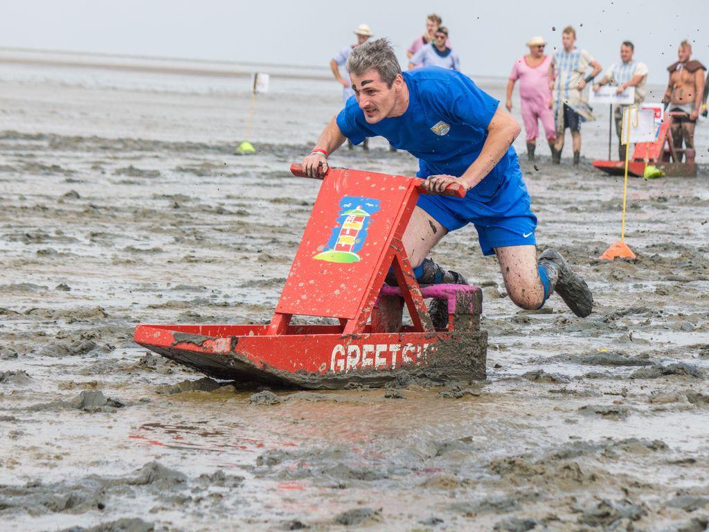 Mann auf einem roten Schlickschlitten während dem Schlickschlittenrennen
